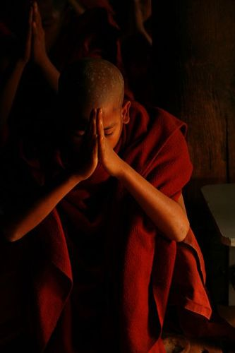 Buddhist monk praying, Myanmar photo via Flickr by Eric Lafforgue