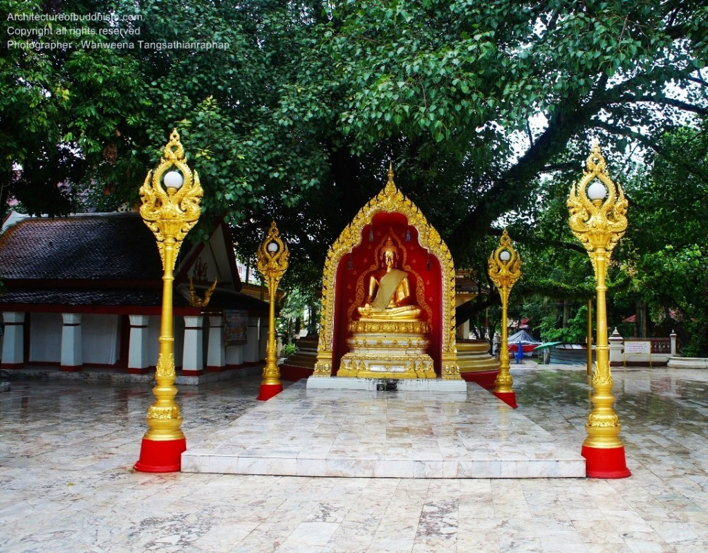 Buddha image sits inside the niche under Bodhi tree