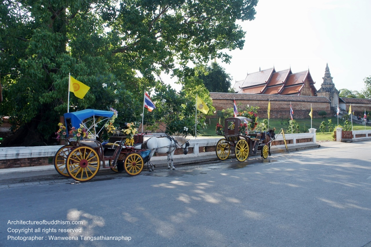 Horse-drawn carriages are parked in front of the temple gate. Interesting to try one?